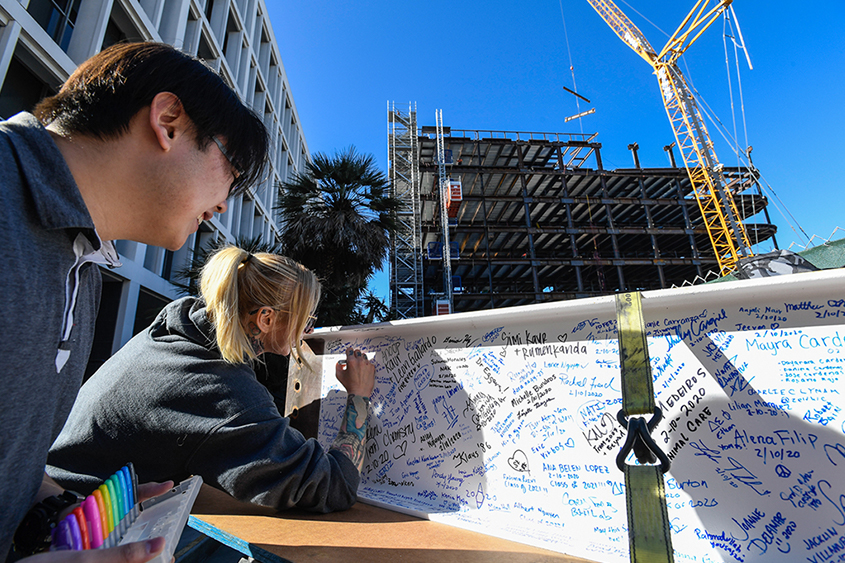 SJSU students signing the last beam for the ISB building.