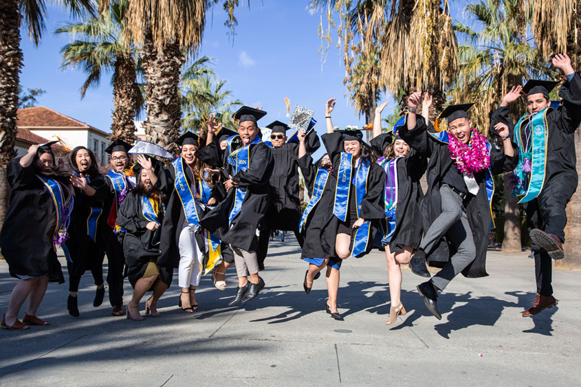 SJSU graduates jumping up in the air.