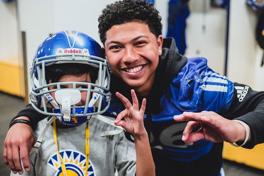 Football player and young student display spartan up hand gesture.
