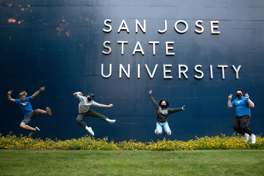SJSU students in masks jumping mid-air in front of the WSQ building.
