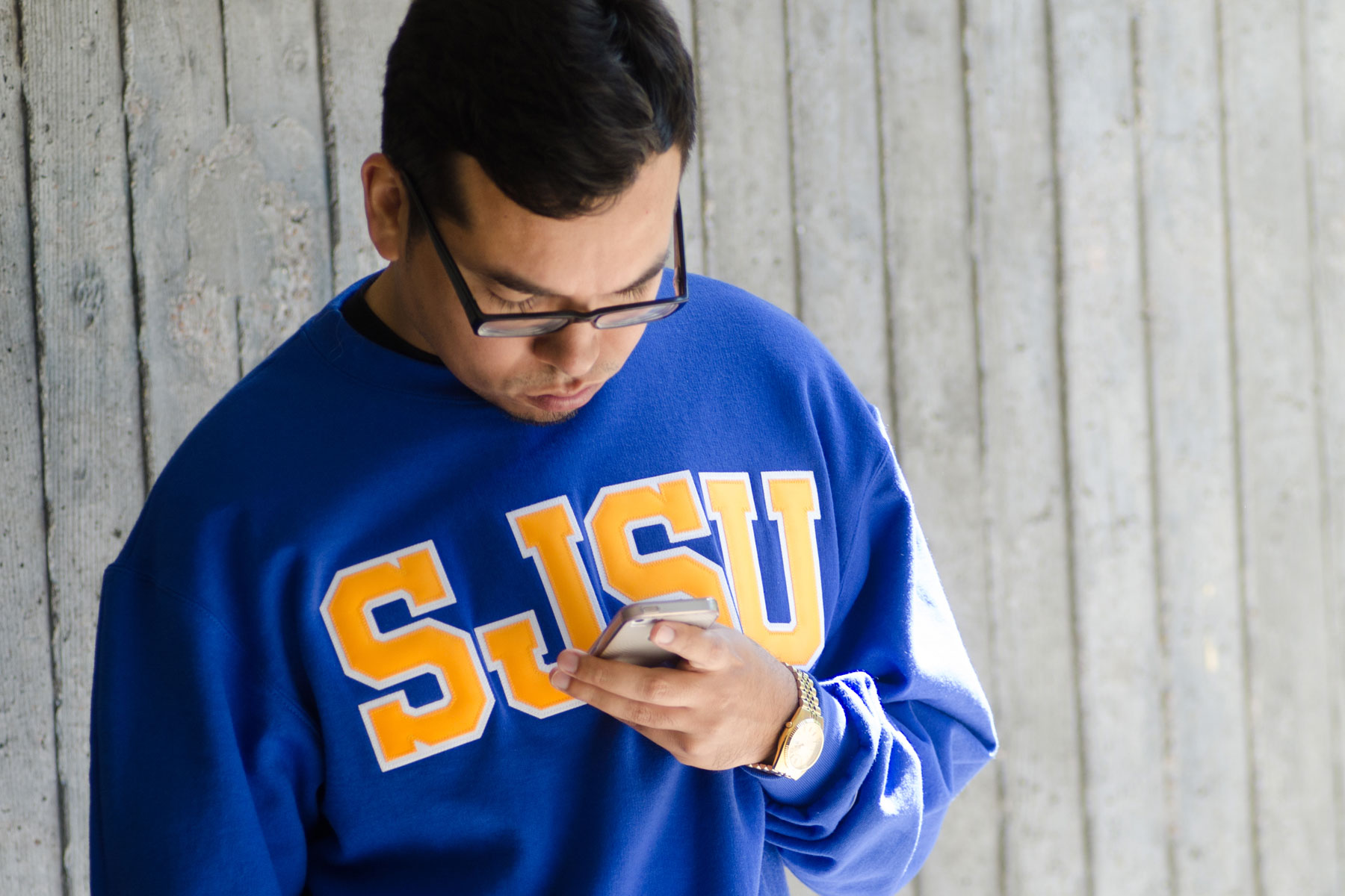SJSU Student on his phone receiving emergency alerts.