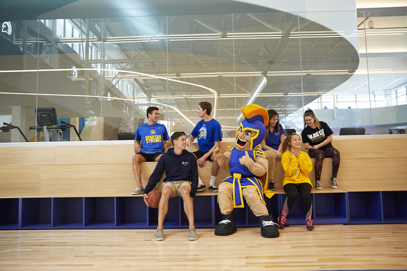 Students sitting with Sammy Spartan in a gym