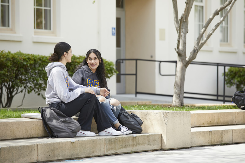 Two students wearing SJSU gear sitting down and talking