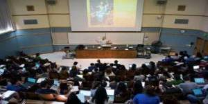 Faculty member giving a lecture in front of a large class in a lecture hall.