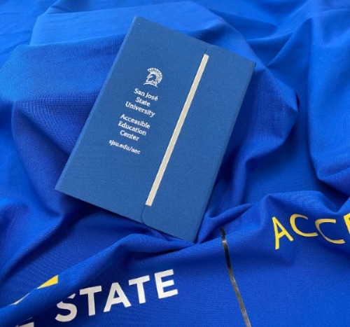 Picture of a Blue Accessible Education Notebook on top of a blue fabric