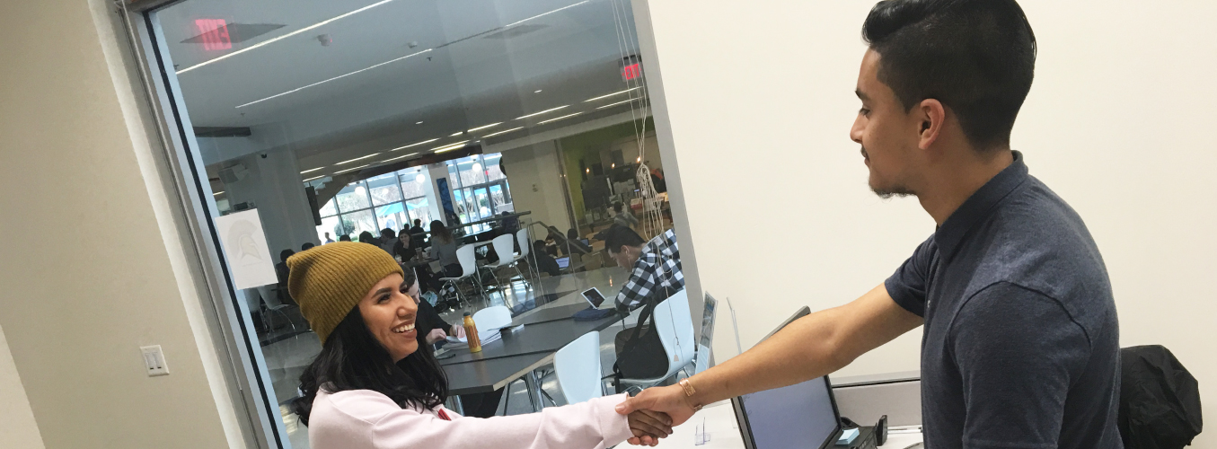Student shaking hands with person at front desk