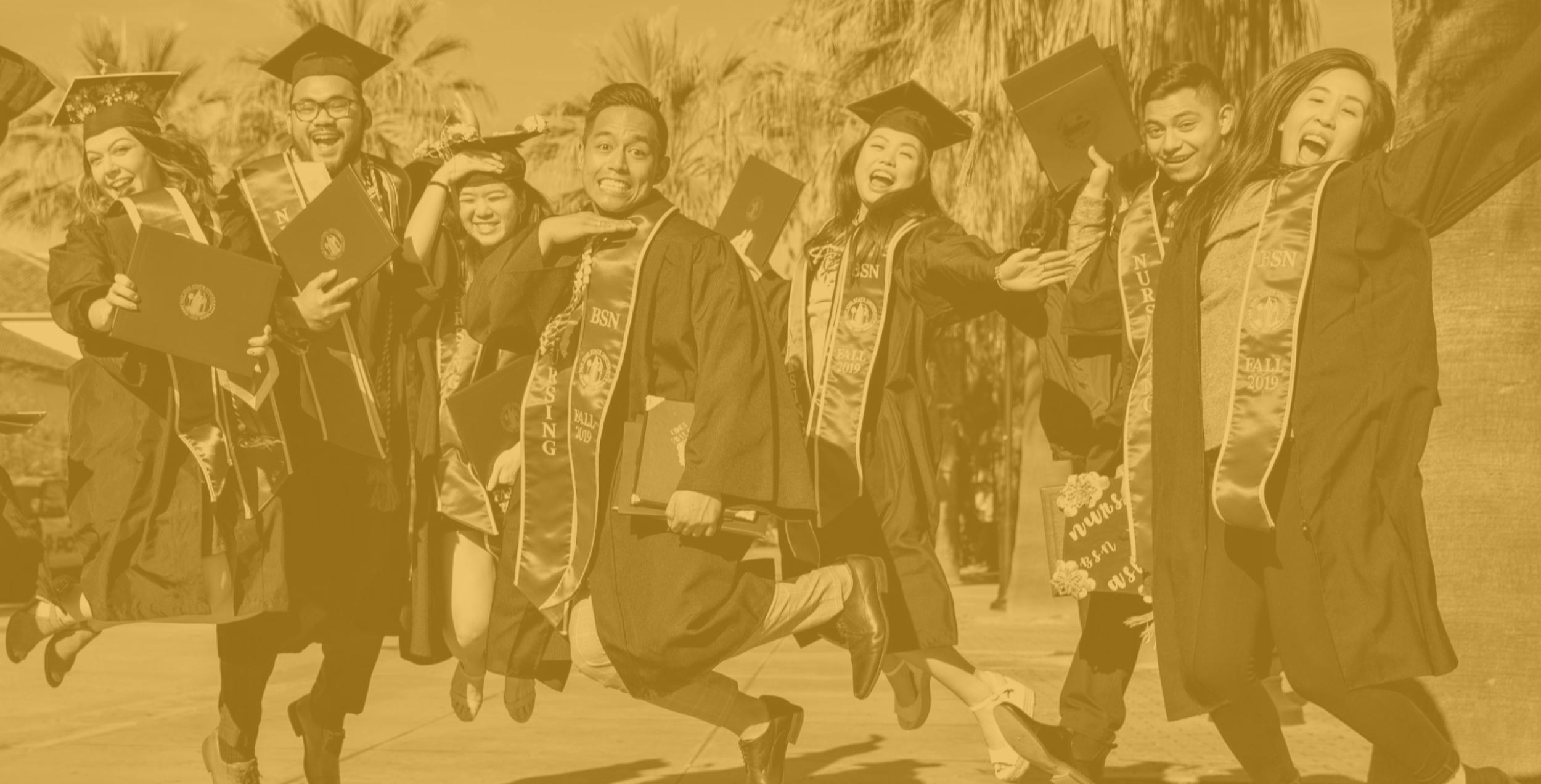 Photo of graduates jumping in the air while wearing academic regalia