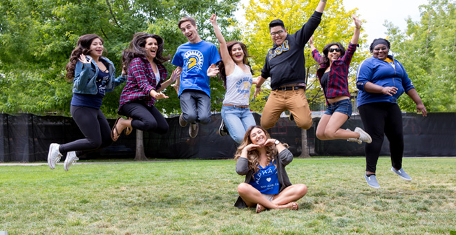 SJSU students jumping in the air and smiling.