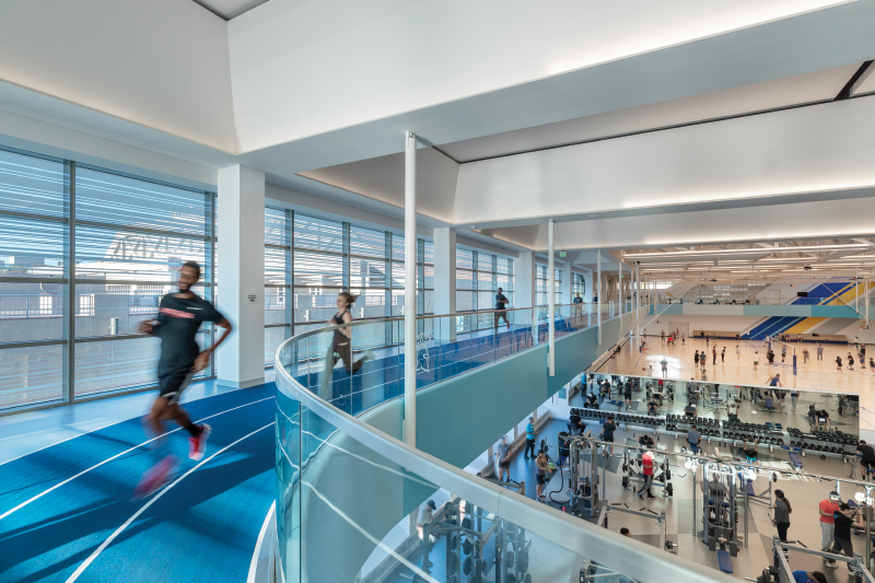 Runners run on 2nd floor track while people lift weights below on the first floor