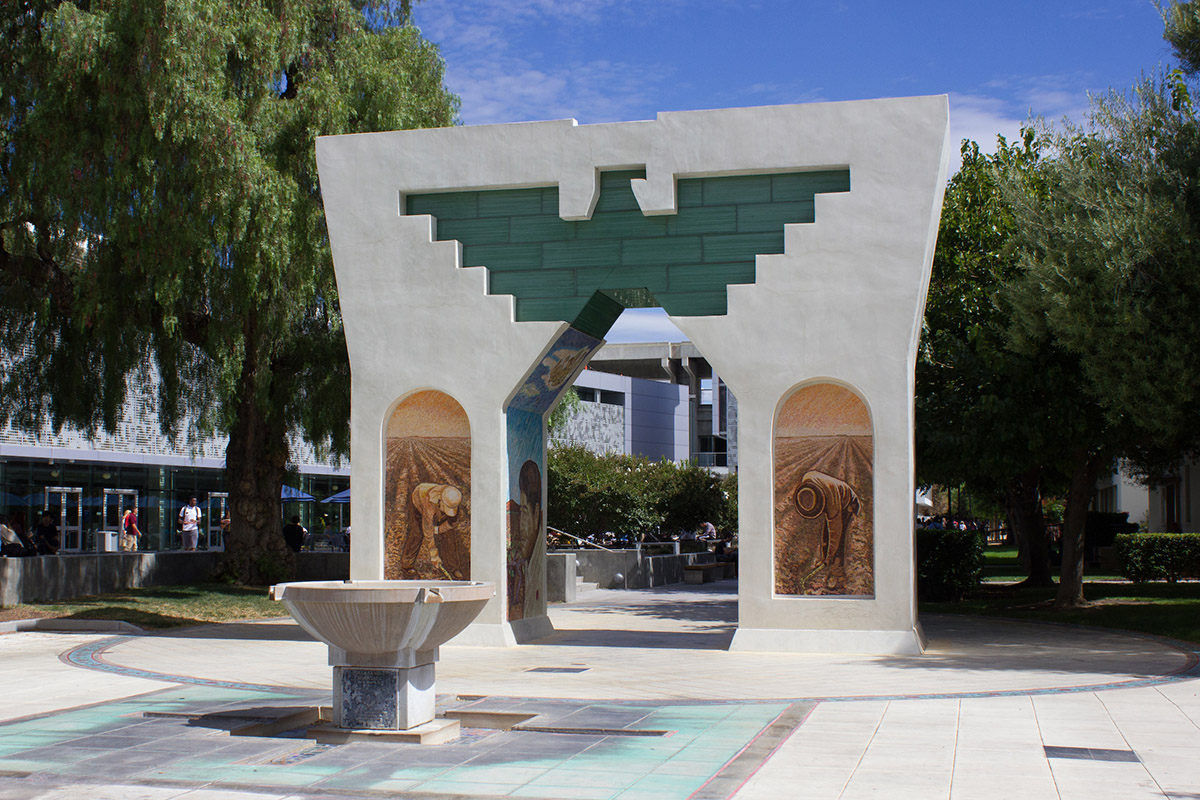 Cesar Chavez arch with farm workers in mosaic tile on each pillar.