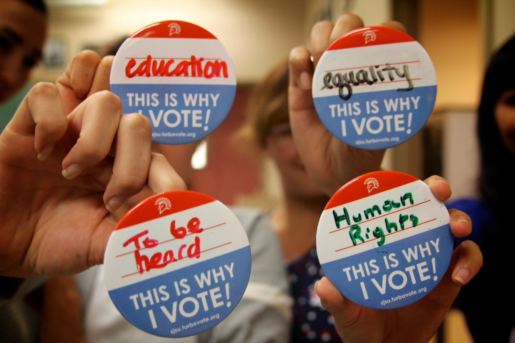 Vote buttons with different messages of why people vote hand written on them.