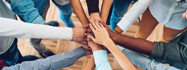 eight people from differnt racial and ethnic groups' arms pointed to a central point with their hands are stacked upon eachother as a team.