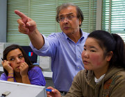 two students and one professor in class, the professor is pointing.
