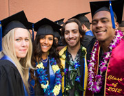 Four students dressed in Academic Regalia at Graduation Ceremonies.