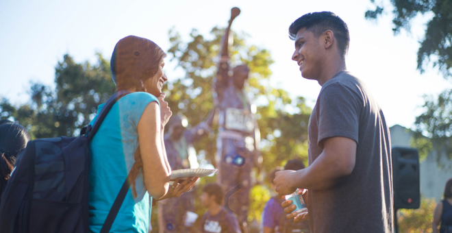 Two students talking in front of the SJSU 1968 Olympics Statue.