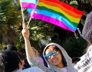 A student waiving a Rainbow-Colored Flag.