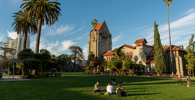 Three people sitting in the grass in front of Tower Hall on the SJSU campus.