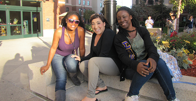 Three students sitting on a bench outside of a building on campus.