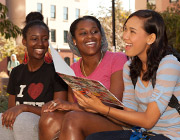Three students smiling while in conversation.