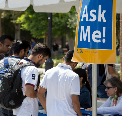 "students at a booth displaying a large ""Ask me"" sign."