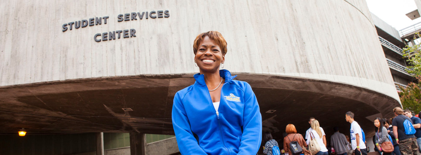 A smiling staff member standing in front of the student services center.