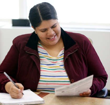 A woman smiles while taking notes.