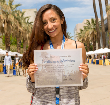 student smiling, holding a certificate of admission to SJSU.
