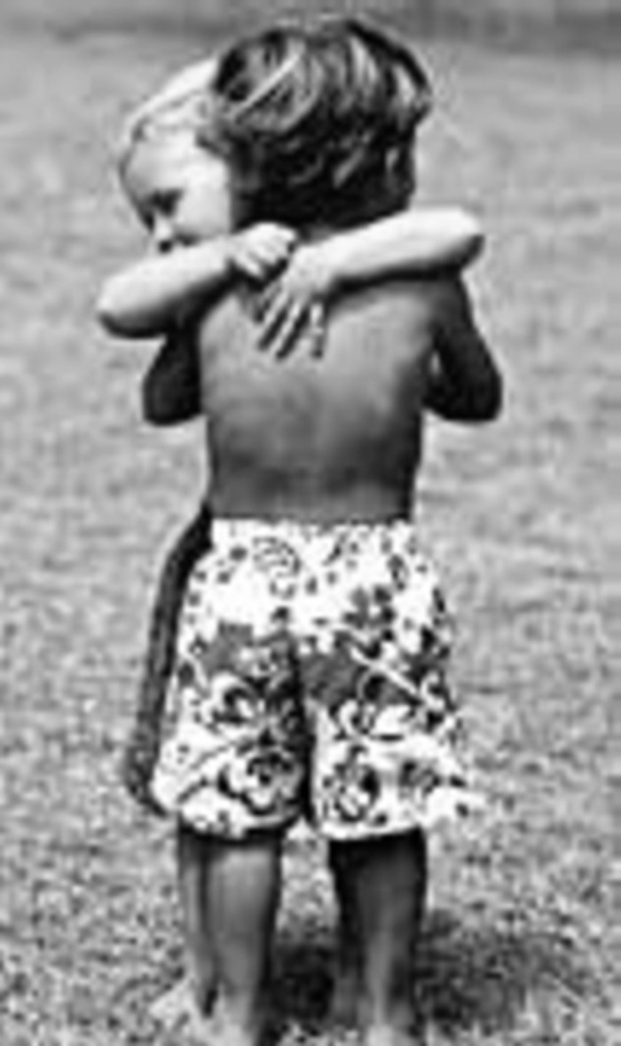 Young black boy hugging young white boy