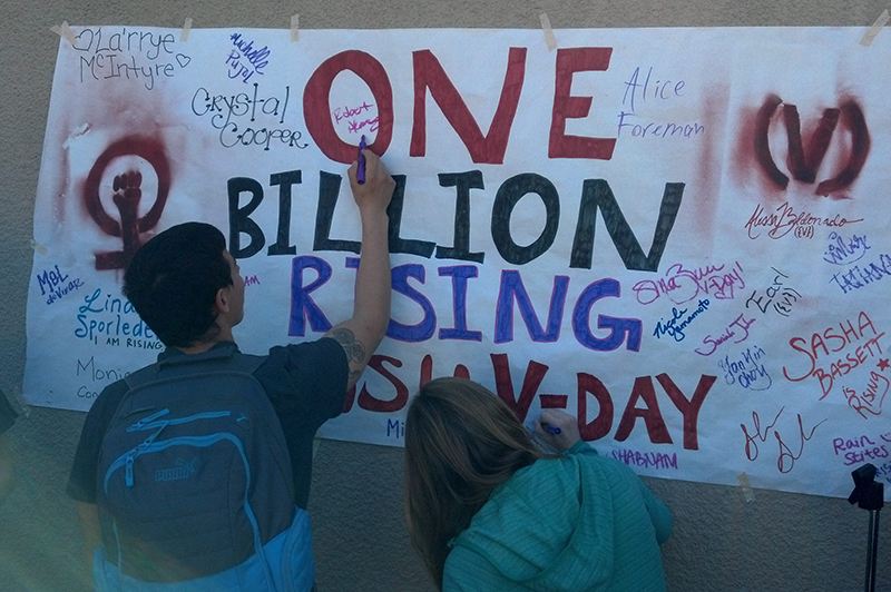 Two students writing on One Billion Rising Poster
