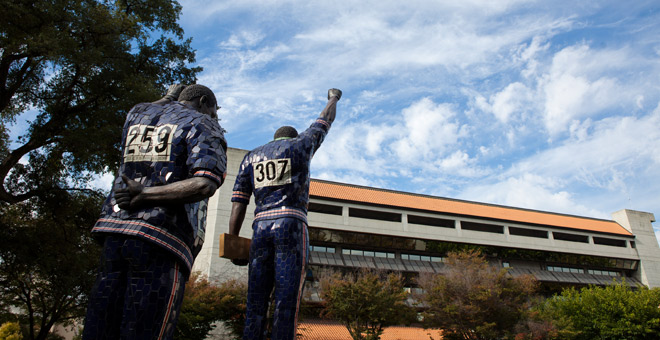 Statue of SJSU track stars Tommie Smith and John Carlos triumphantly raising their fists while standing on an Olympic podium.