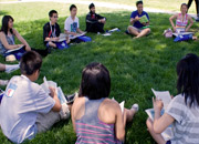 Student's sitting in a circle on the grass on campus.