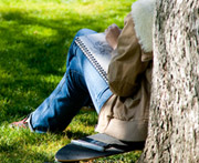A student sitting against a tree studying.