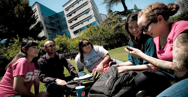 A diverse group of students sitting on the lawn in front of the MLK Library at SJSU.
