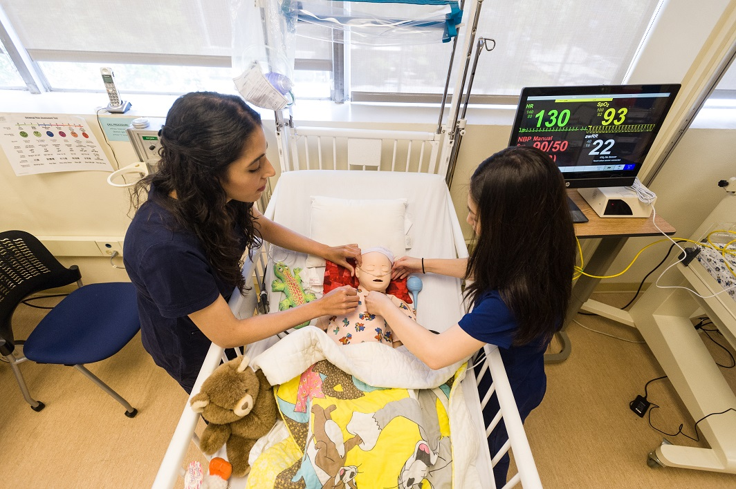 Nursing students working with a simulated-baby in a hospital crib