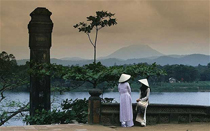 Two women talking by Vietnam landmark