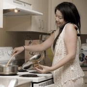 Woman Talking On The Phone While Cooking