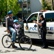 Police officer helping a person and his kid on bicycle