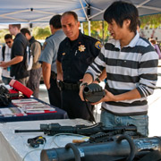 police officer and attendees at safety presentation fair