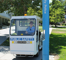 PSA student in electronic cart with sign PUBLIC SAFETY