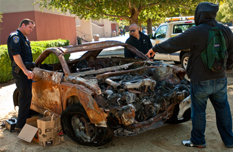 Police officer and two students look at a car total in traffic accident