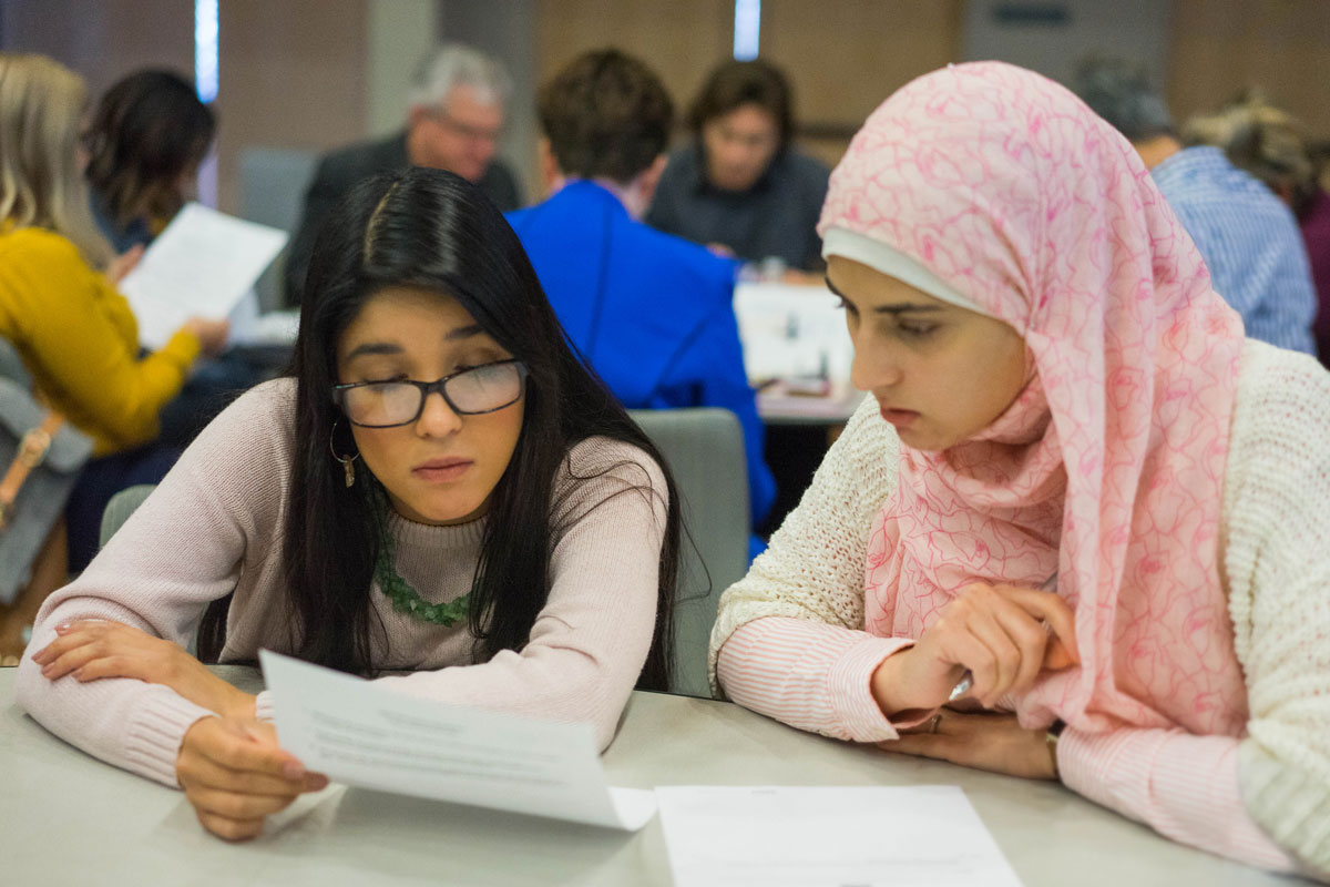 Two female students looking over informational material.