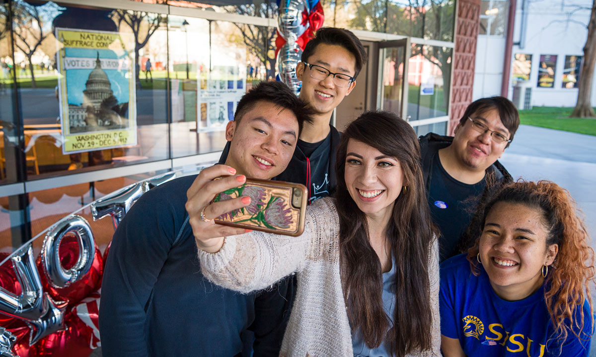 SJSU students huddling together for a selfie at a voting center.