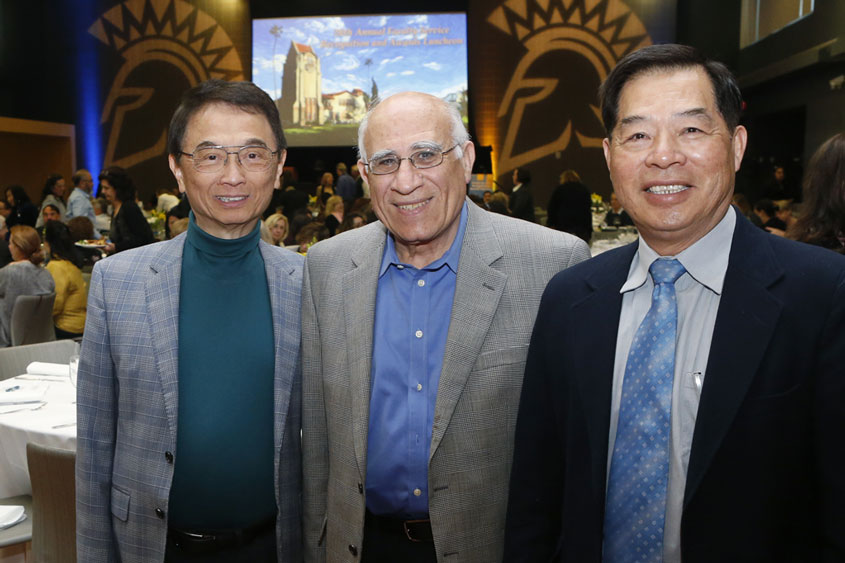 Three male faculty members smiling.