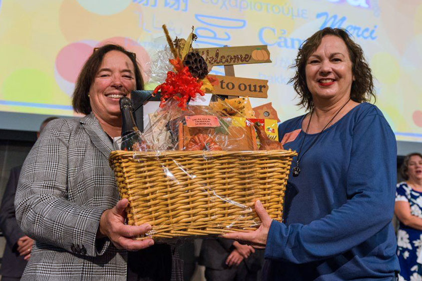 Two staff members holding up a gift basket.