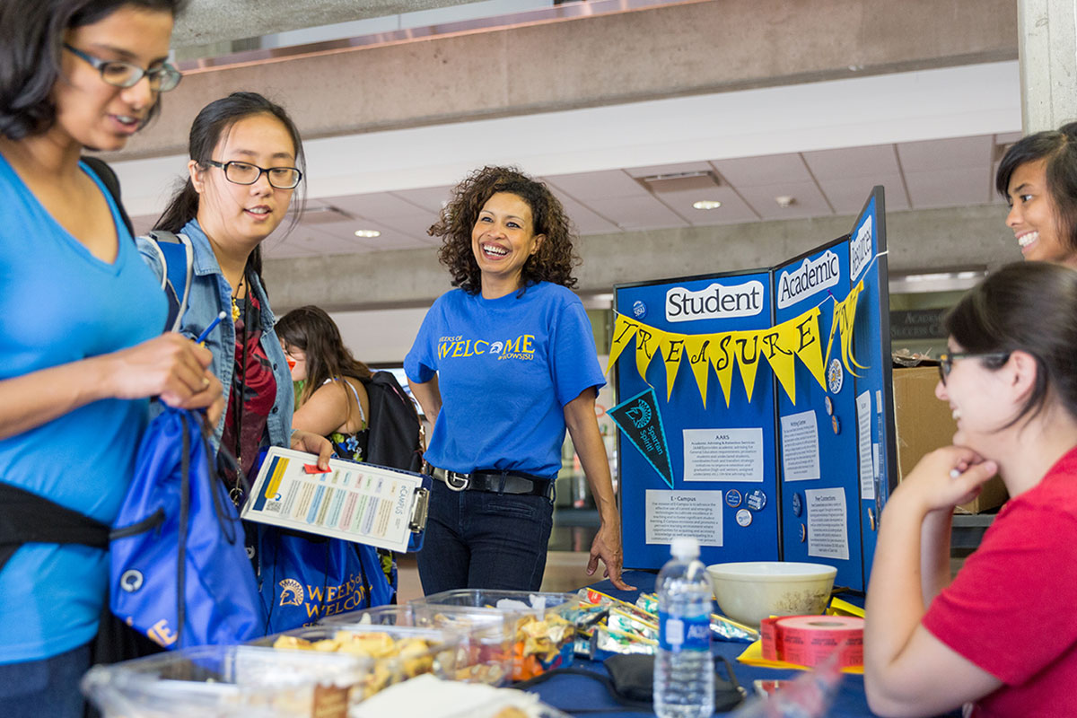Staff member smiling in front of a WOW booth with students.