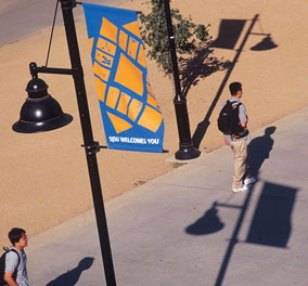 photo: campus welcome signeage with SJSU logo tile artwork on lamposts along El Paseo de Ceasar Chavez