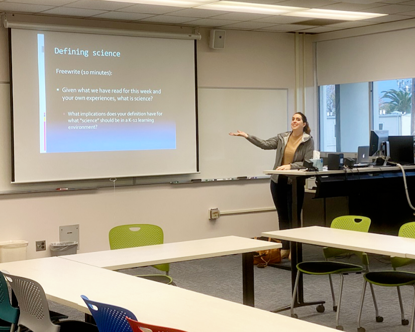 Image of Elly in a class room in front of a projector