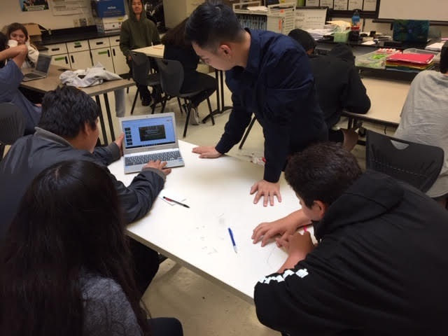 Image of a teacher helping students on their laptop