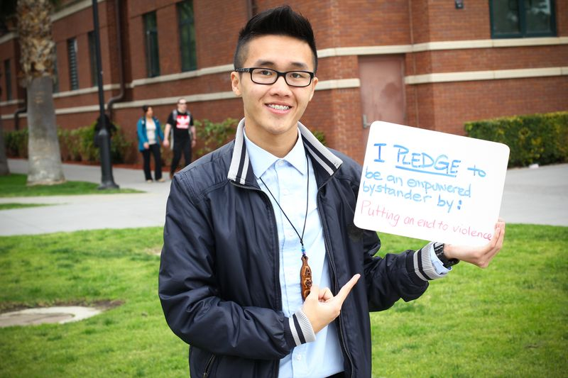 Male Asian student holding sign: I pledge to be an empowered bystander by: Putting an end to violence