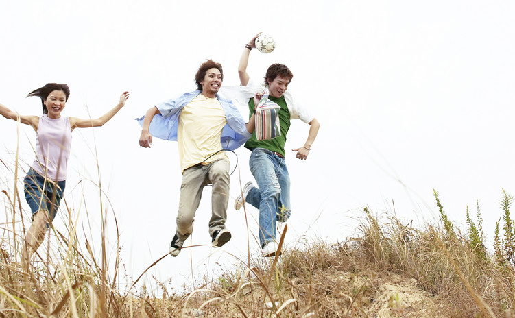 3 friends jumping though a dry grass field